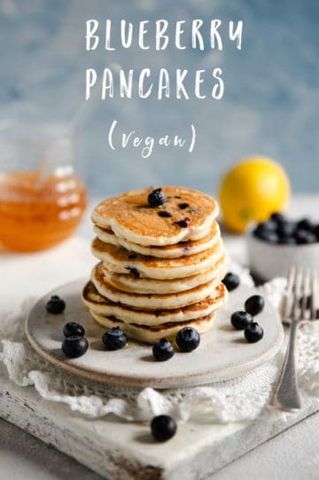 Stack of blueberry pancakes on a small white plate with some fresh blueberries on site