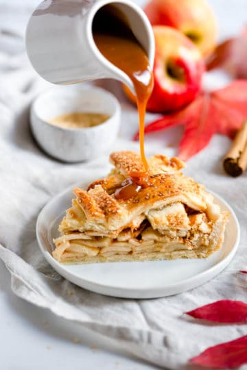 a slice of an apple pie with caramel being poured on it