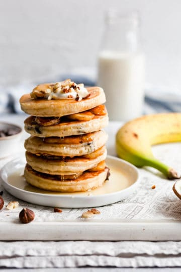 Side close up of a stack of 5 hazelnut pancakes with maple syrup