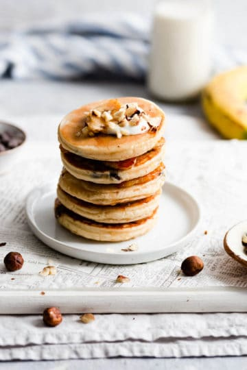 side view of a stack of pancakes topped with yogurt and hazelnuts