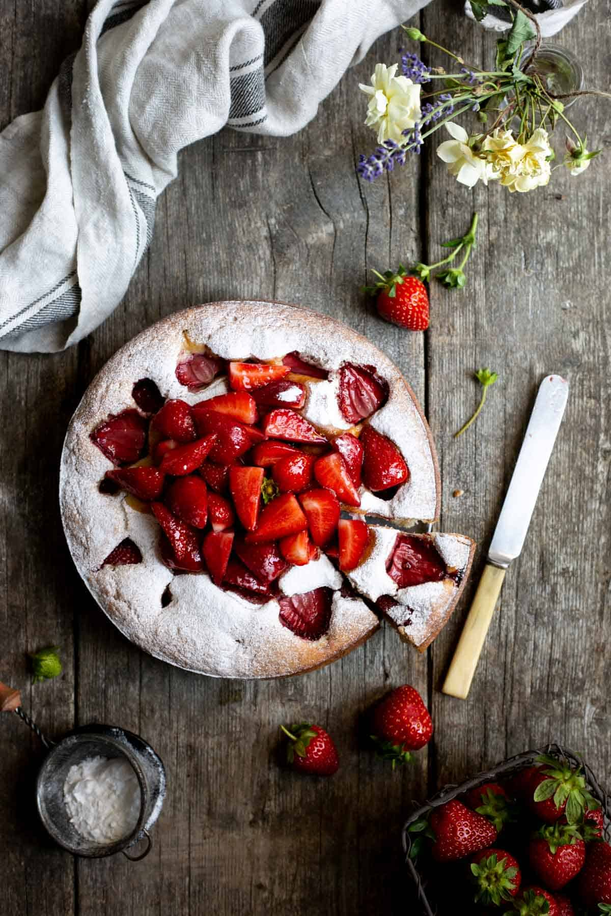 Fresh strawberry yogurt cake covered in icing sugar