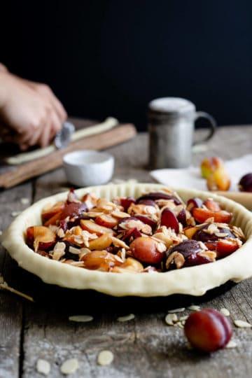 Unbaked plum pie with almonds