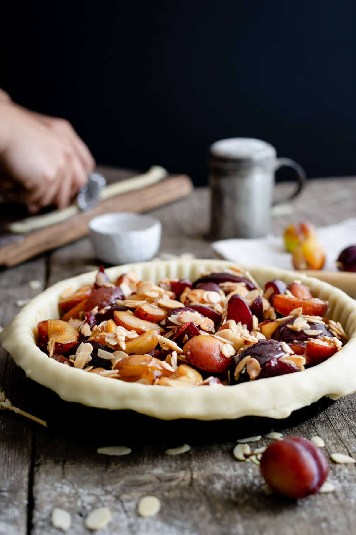 Unbaked plum pie with almonds