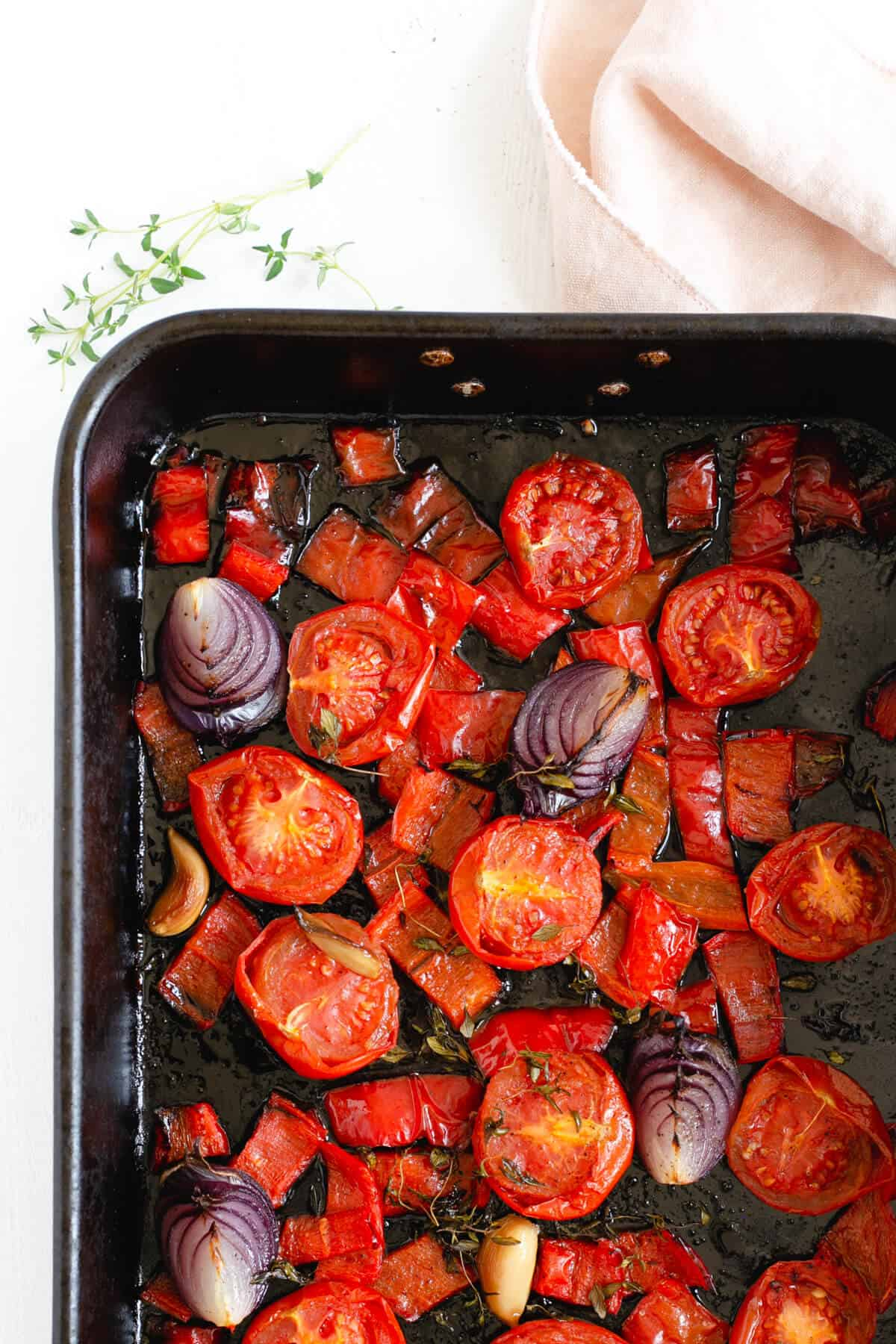 Roasted tomatoes, red peppers and red onions in a roasting tin