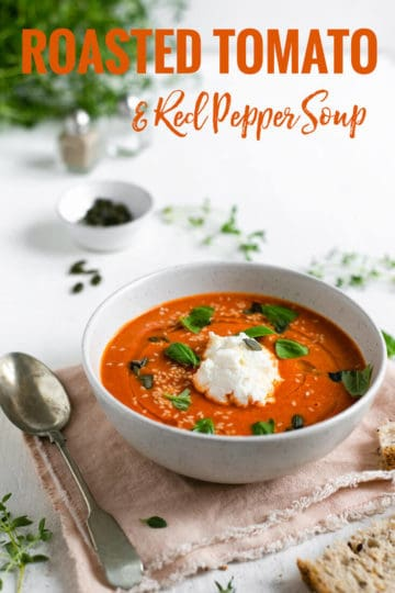 A bowl of roasted tomato soup topped with fresh basil and toasted seeds