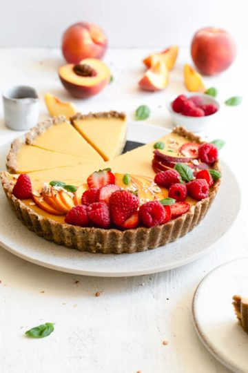 Front on photo of vegan peach tart topped with fresh peach and summer berries