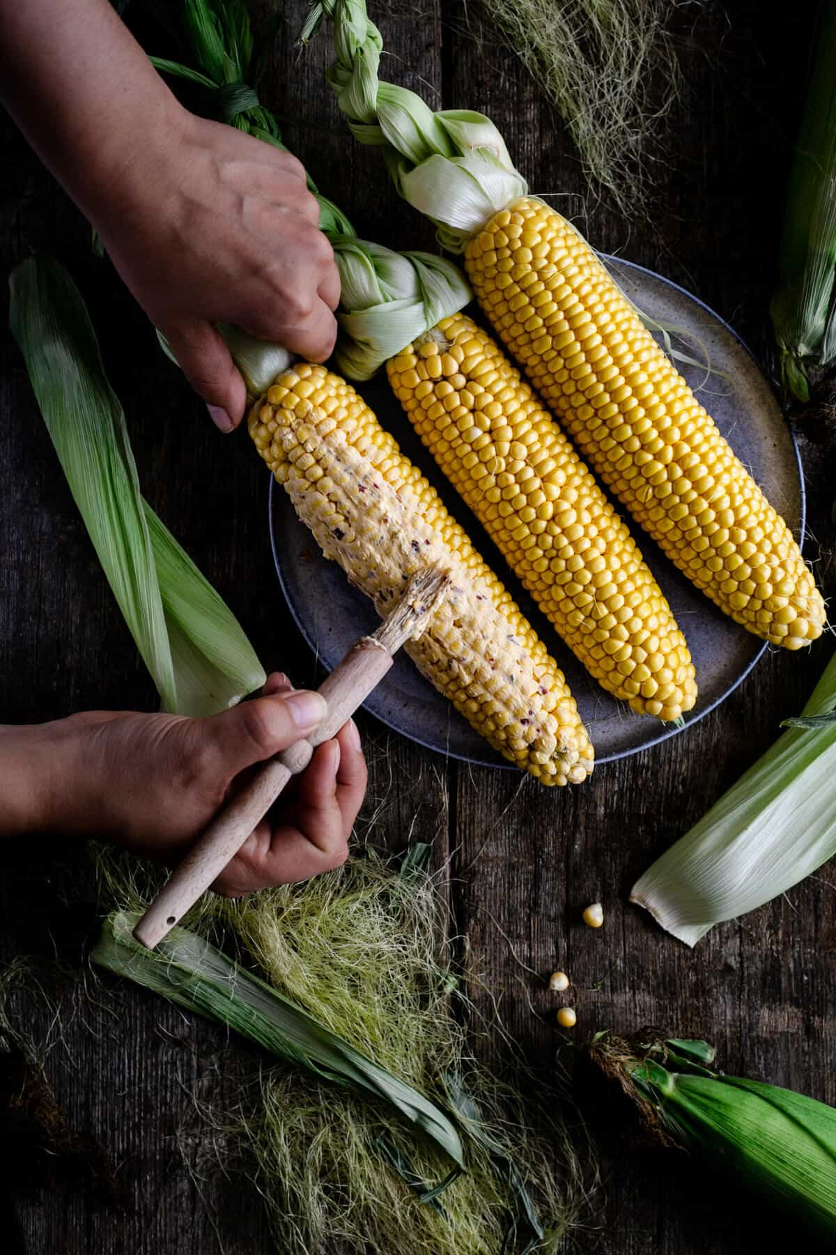 Spreading chilli-infused butter on cobs of corn with pastry brush