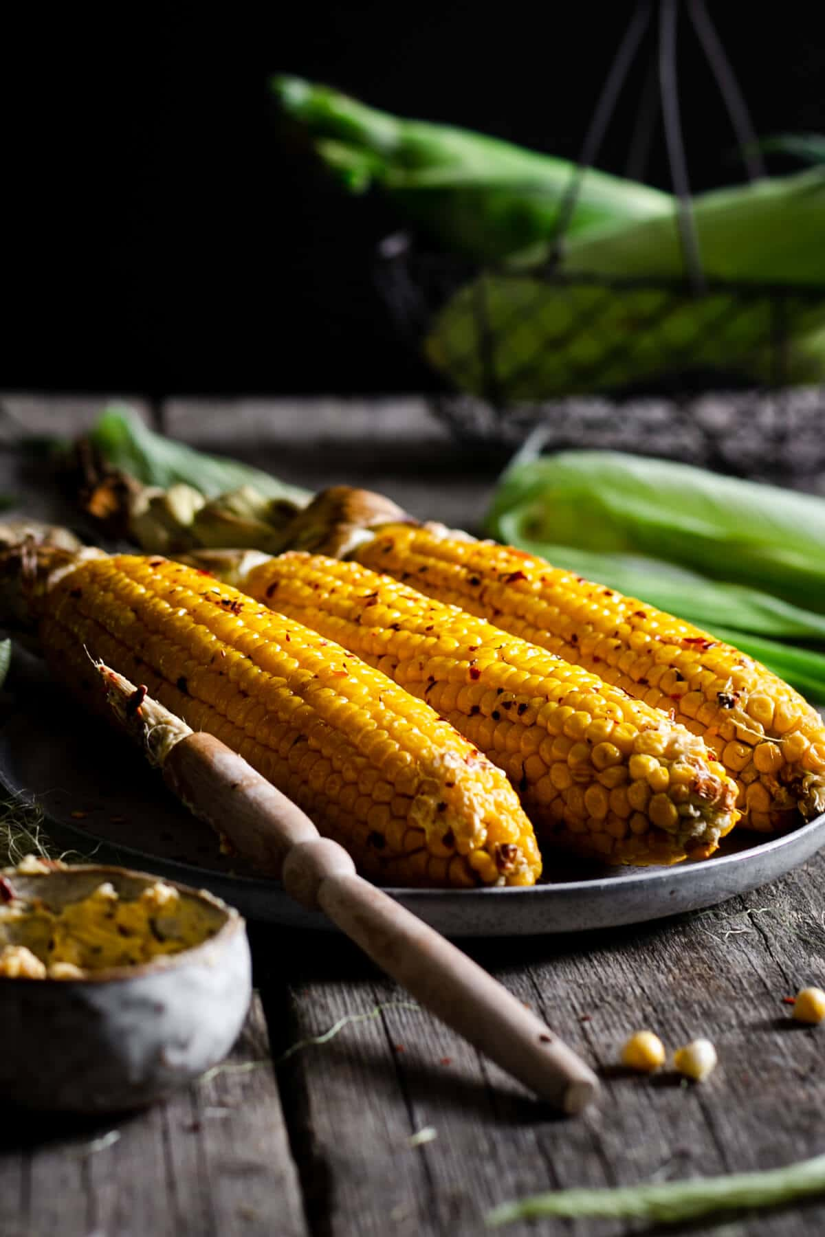 Three corn cobs on the plate with chilli butter