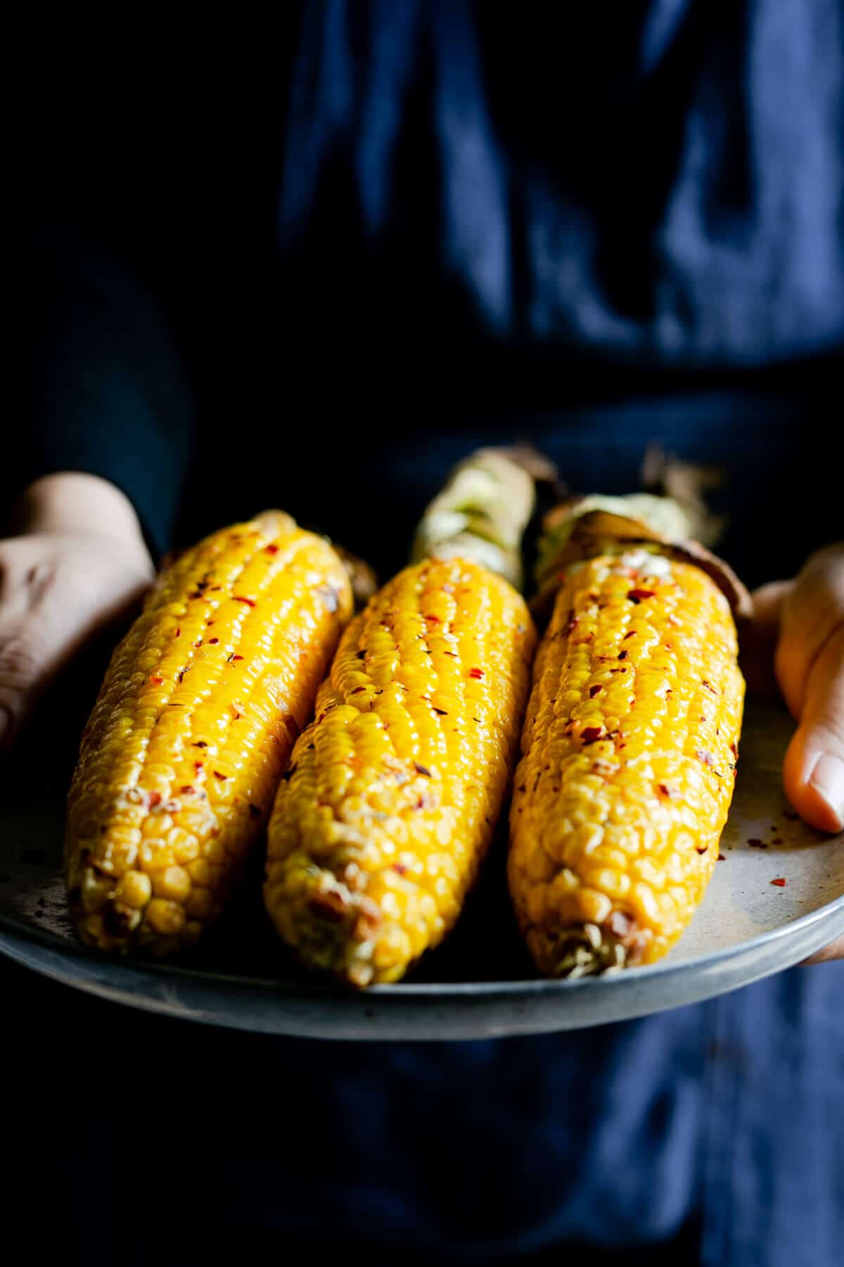 A person holding a plate with cobs of corn in chilli butter