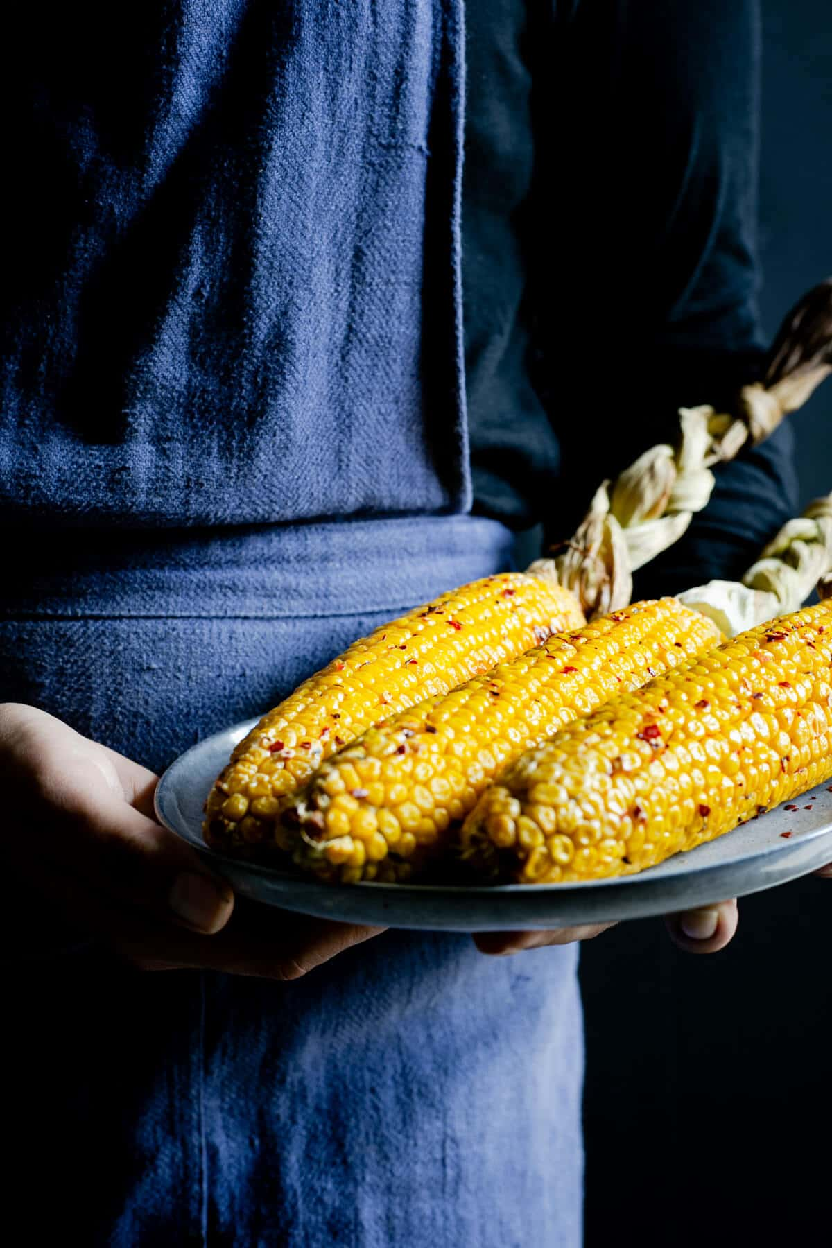 A person holding a plate with buttered corn on the cob