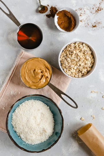 Overhead shot of bowl of oats, shredded coconut, peanut butter, maple syrup and mixed spice