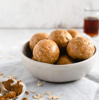 A straight-on angle shot of small bowl filled with coconut and peanut butter spiced energy bites with small jar of maple syrup in the background