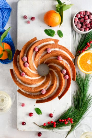Overhead shot of orange and cranberry bundt cake, drizzled with icing and topped with sugared cranberries