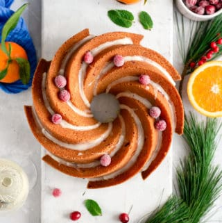 Overhead shot of orange and cranberry bundt cake topped with some icing and sugar covered cranberries