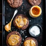 Overhead shot of five big chocolate salted caramel cookies on a baking tray with small bowl of sea salt and small jar of caramel