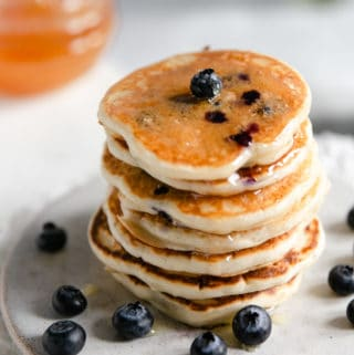 Stack of blueberry pancakes drizzled with honey on a small plate