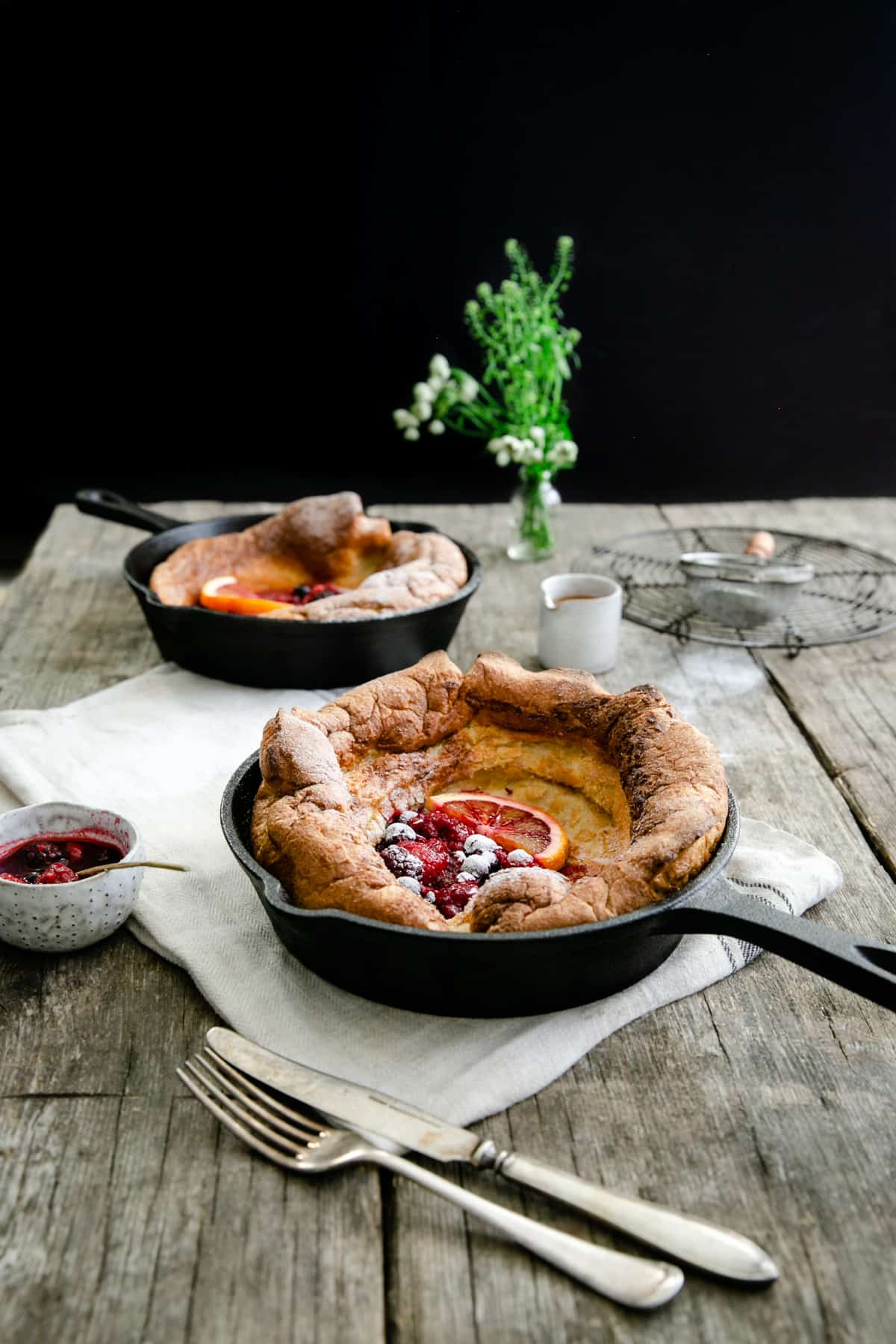 Two small skillets with mixed berry Dutch babies on a wooden table with