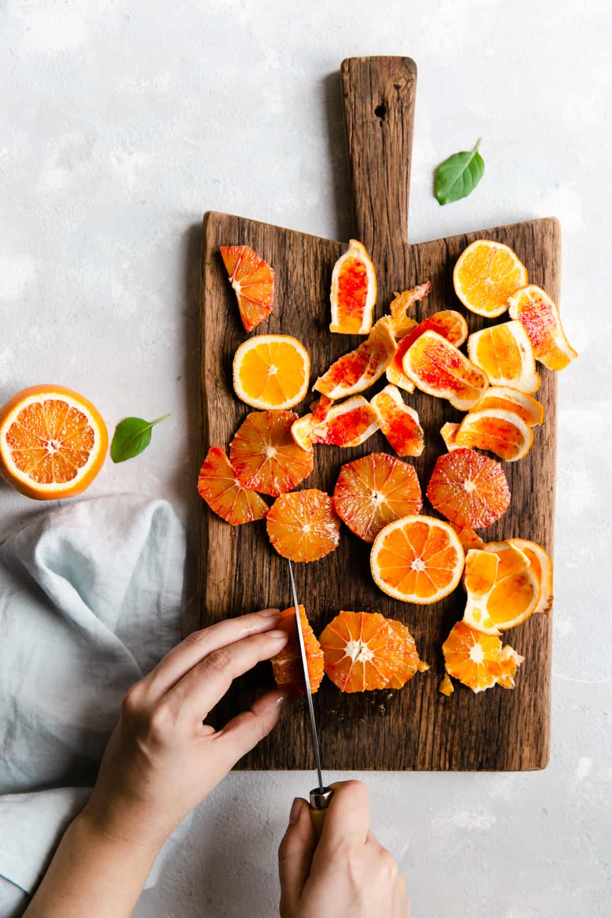 overhead shot of a person slicing a blood orange on a wooden chopping board