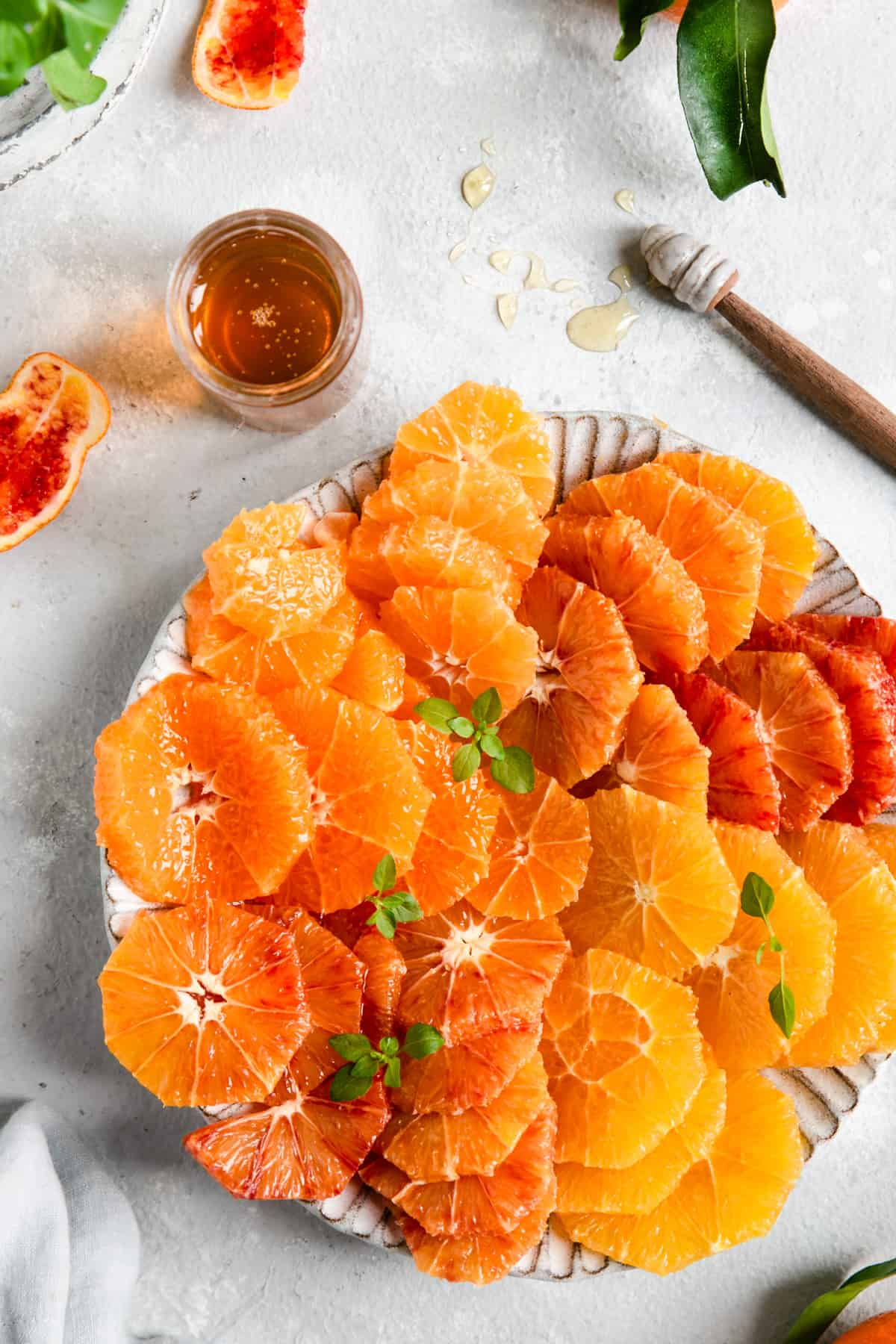 plate full of sliced citrus and small jar of honey on side