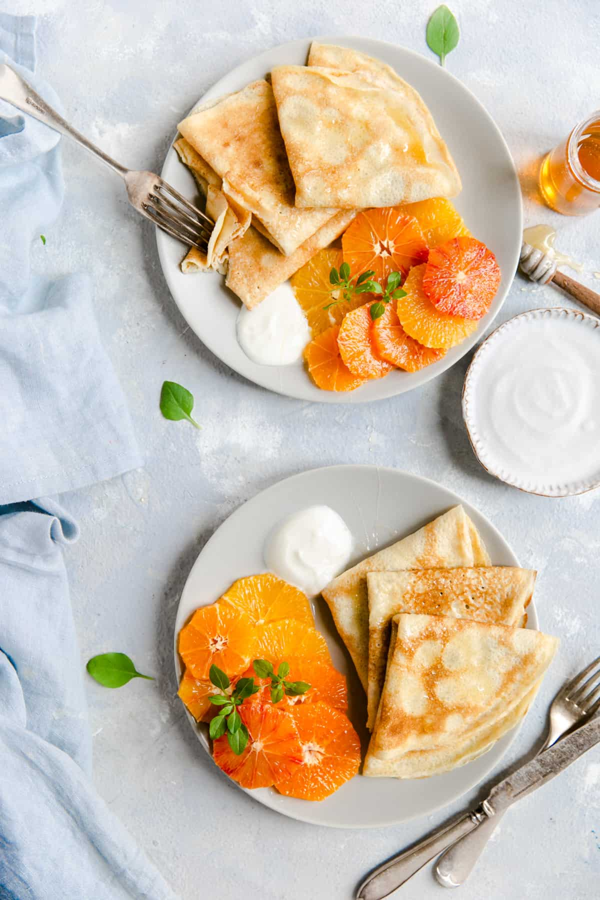 overhead shot of two plates with crepes, citrus, yogurt and honey drizzle