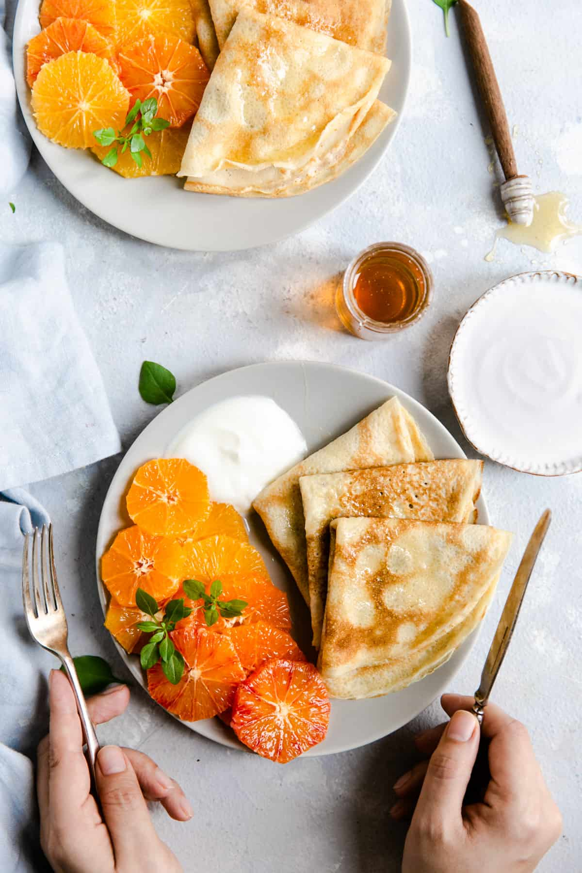overhead shot of a plate with crepes, citrus slices and yogurt with honey