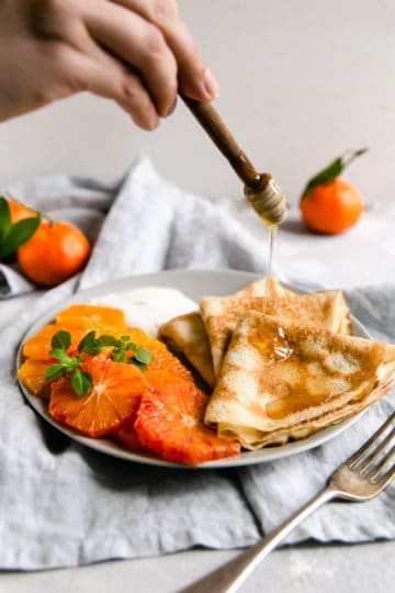 a person drizzling some homey over a plate with crepes and citrus