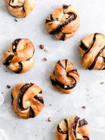 Overhead shot of baked chocolate hazelnut babka buns on a white background