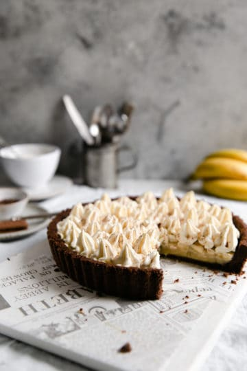 Straight ahead shot of chocolate coconut banoffee pie with a slice missing