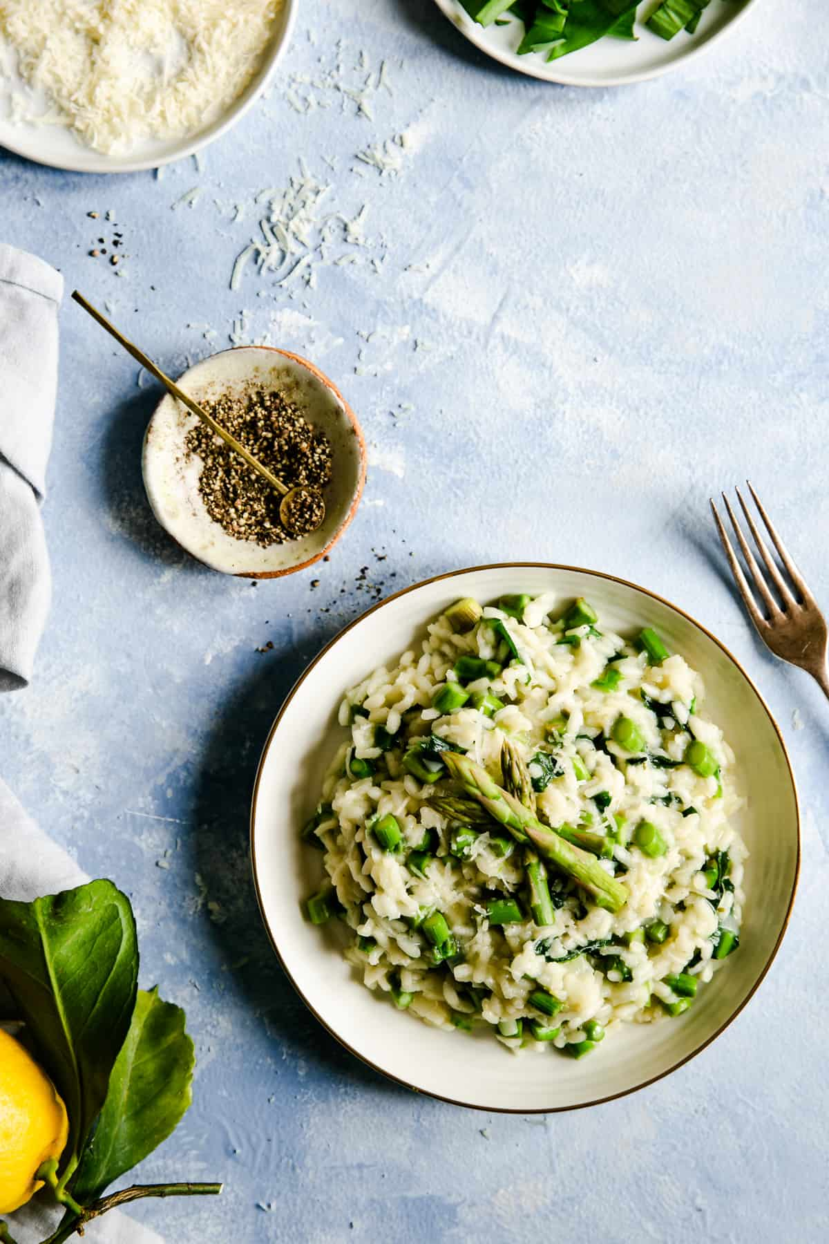 Overhead shot of a bowl with wild garlic and asparagus risotto with small side dish with black pepper