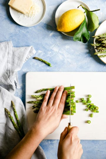 overhead shot of a person chopping the green asparagus on a white chopping board