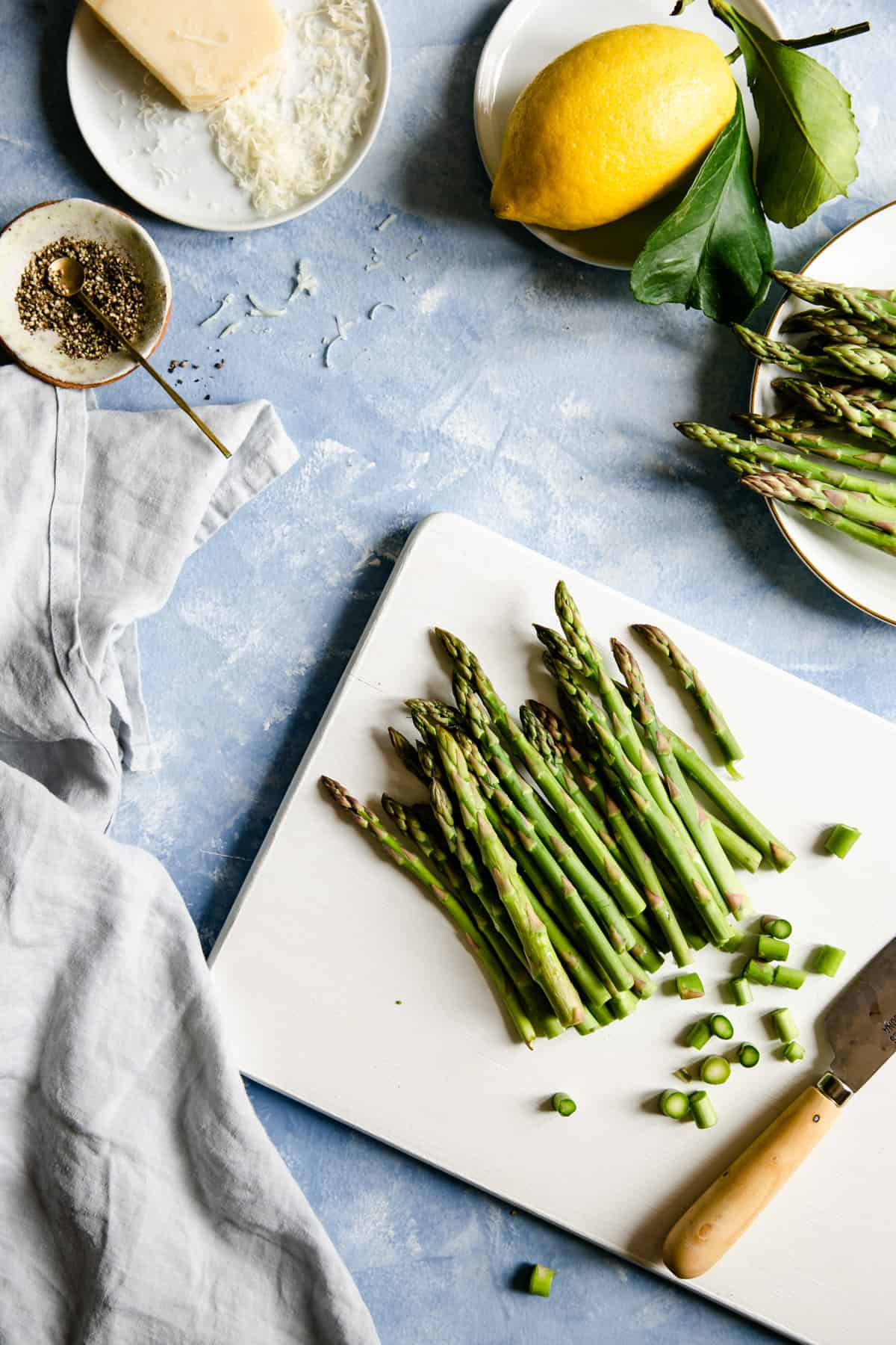 overhead shot of chopped asparagus on a white chopping board