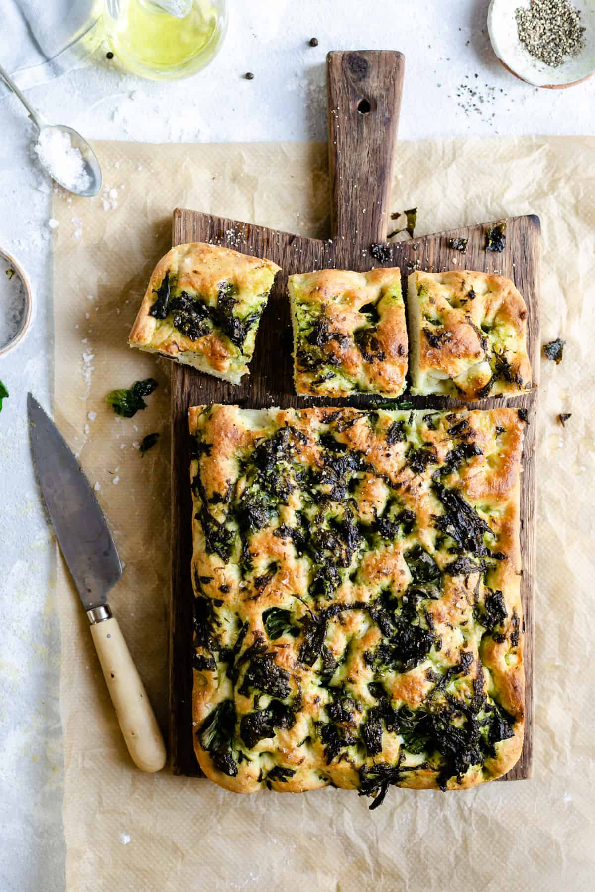 overhead shot of wild garlic and black pepper focaccia on a wooden chopping board