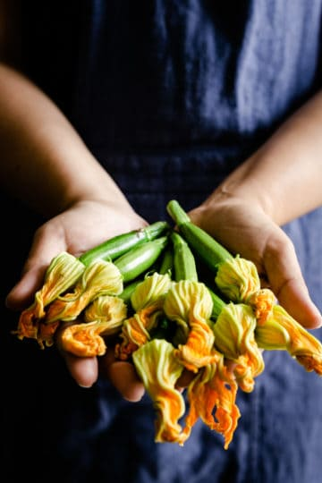 a person holding courgette flowers in their hands
