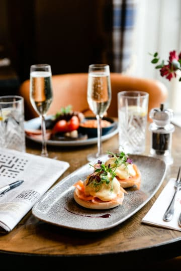 side angle shot of brunch scene with eggs royal and prosecco glasses in the background
