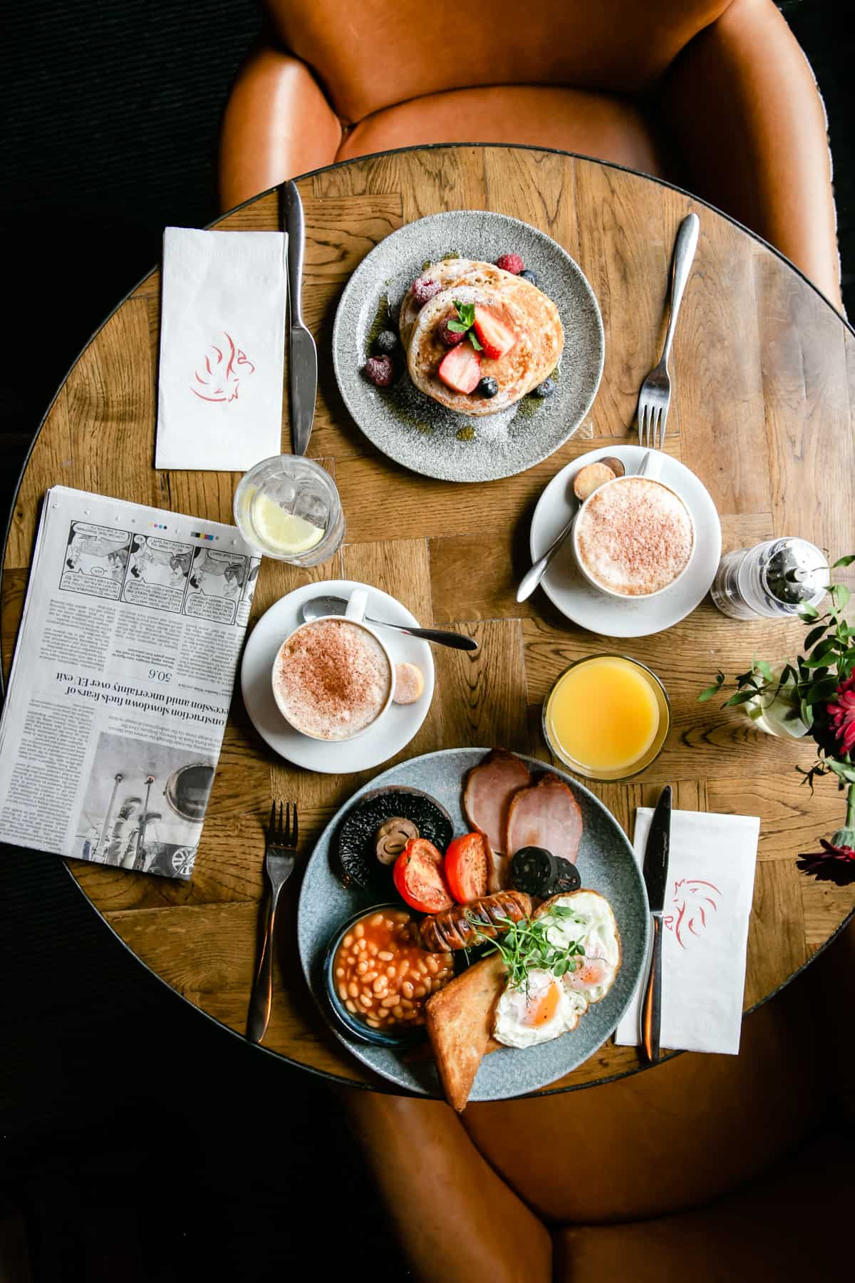 overhead shot of a round table with breakfast dishes and coffee