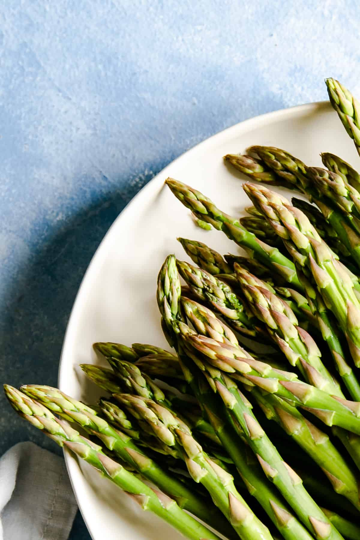 close up of green asparagus tips in a white plate on a blue backdrop