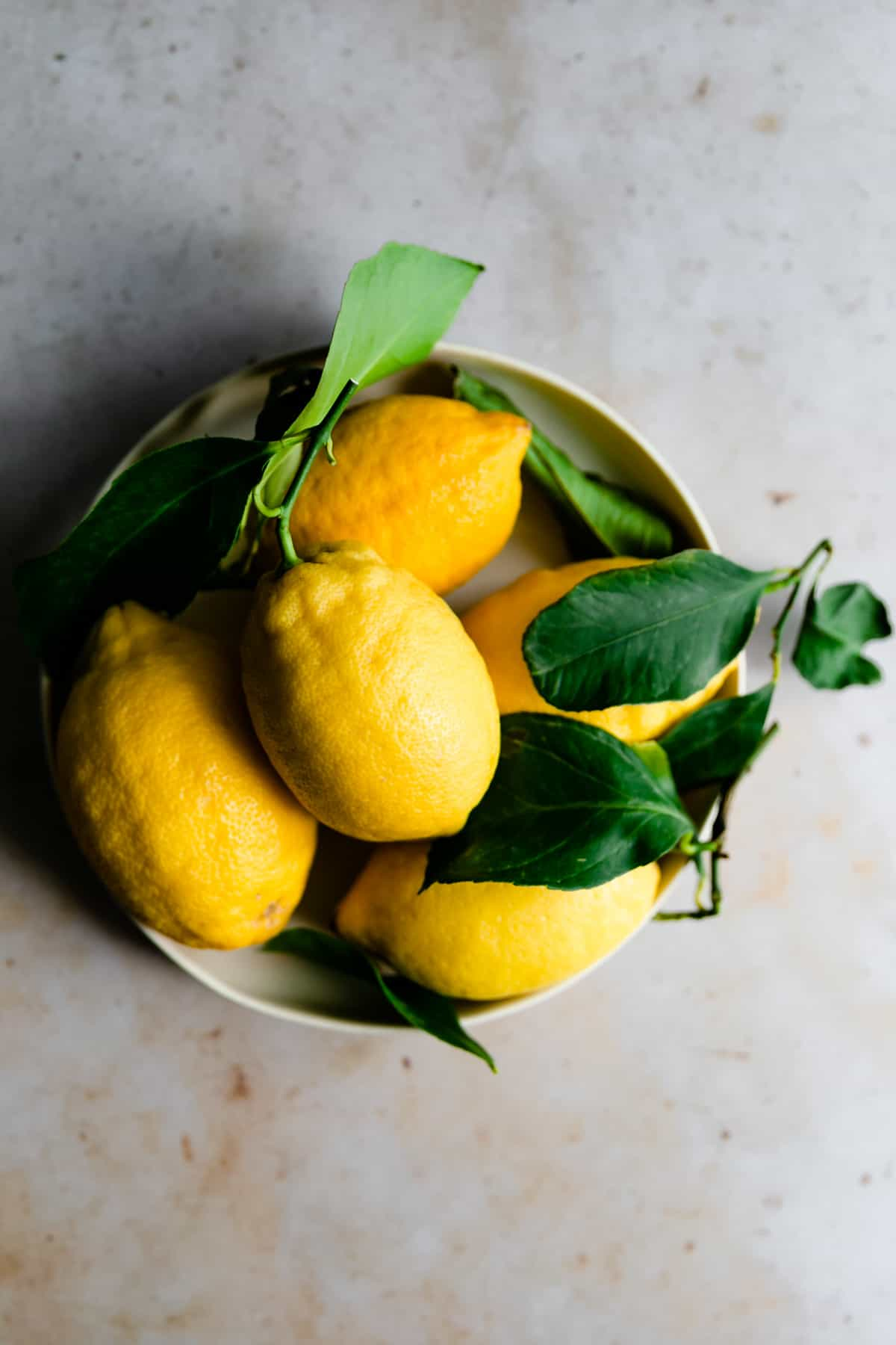 overhead shot of Sorrento lemons with leaves in a small bowl