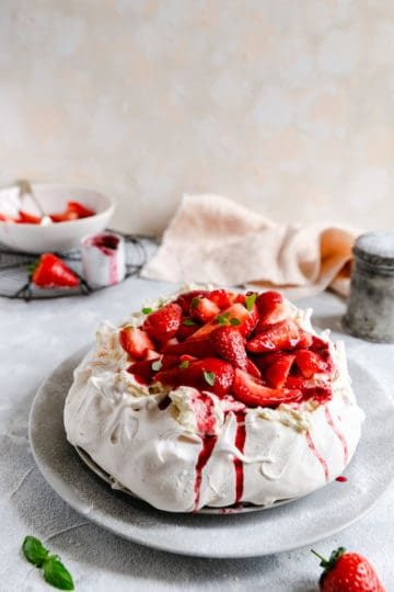 straight ahead shot of strawberry Pavlova on a large plate dusted with icing sugar