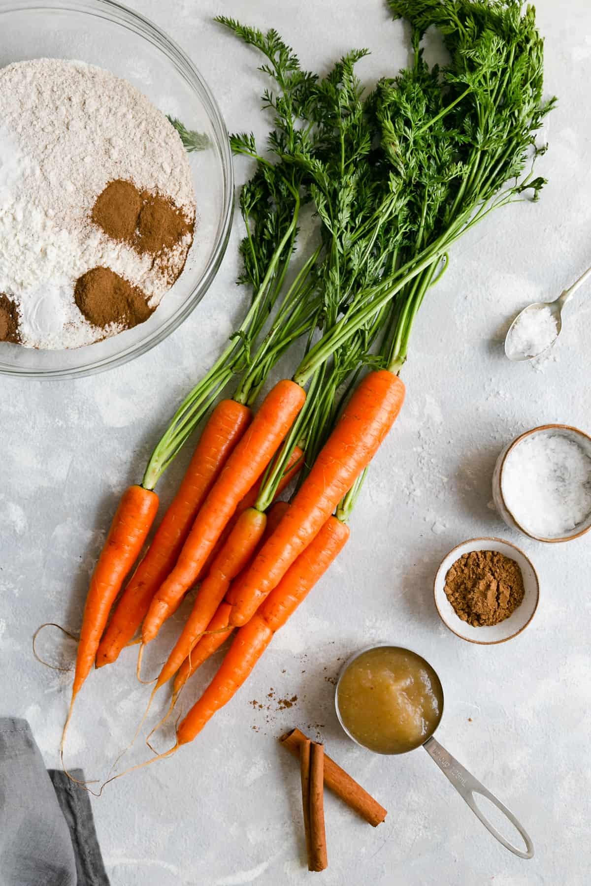 overhead shot of some of the carrot cake ingredients: carrots with tops, flour, apple sauce and spices