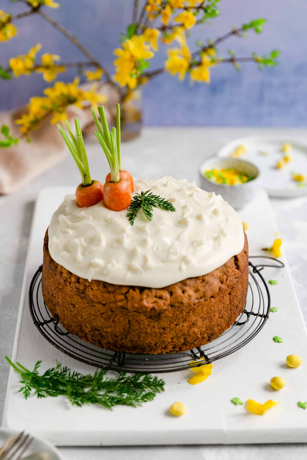 45 degree angle shot of the easy vegan carrot cake on a round metal cooling rack with some yellow flowers in the background