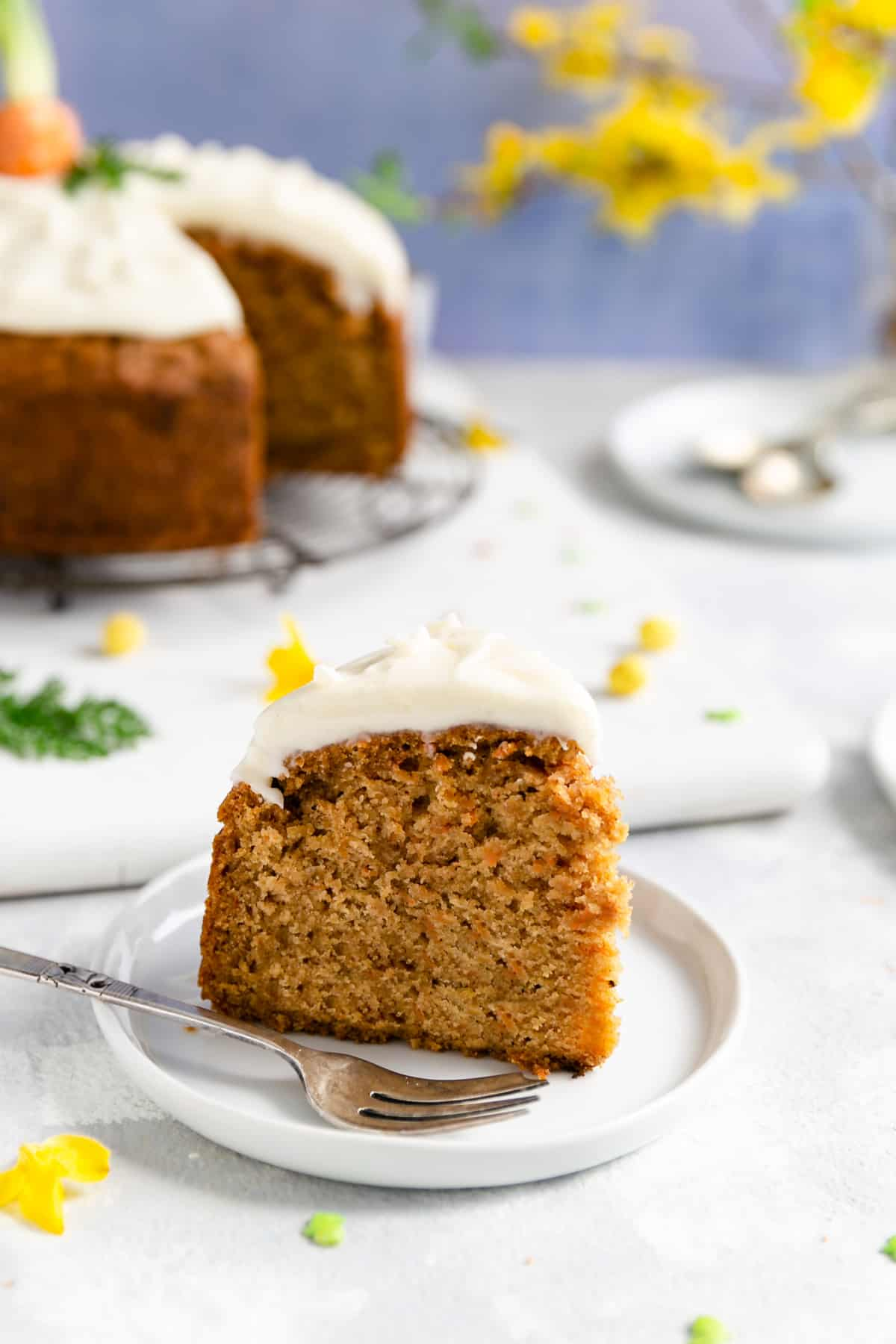 side shot of a slice of the carrot cake served on a small white plate