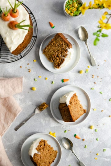 overhead shot of three individual carrot cake slices served on small white plates and some cutlery on side