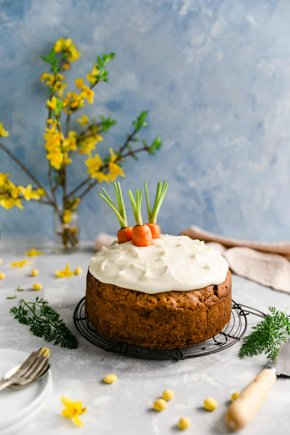 Vegan carrot cake topped with cream cheese frosting and some carrot tops