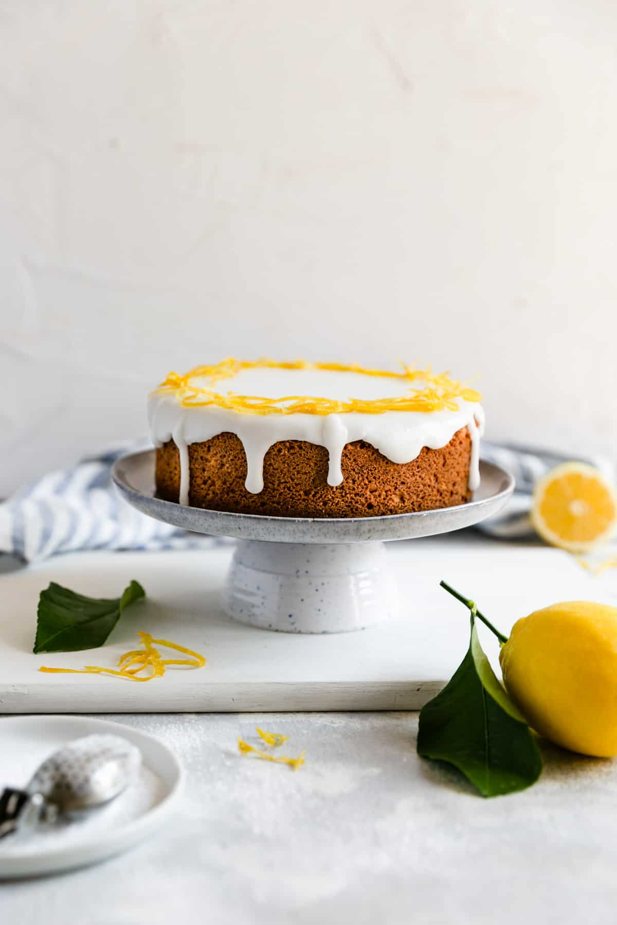 a straight ahead shot of a whole zesty lemon cake on a cake stand