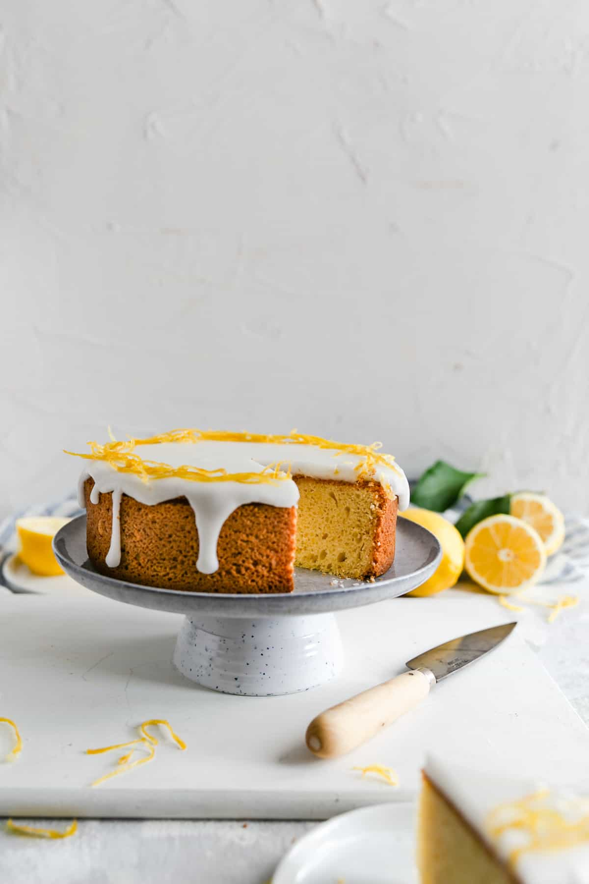 a straight ahead angle shot of a zesty lemon cake on a cake stand with one piece cut out