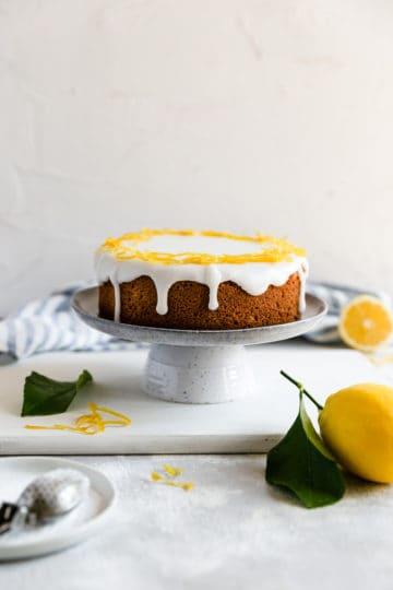a straight ahead shot of a whole zesty lemon cake on a cake stand