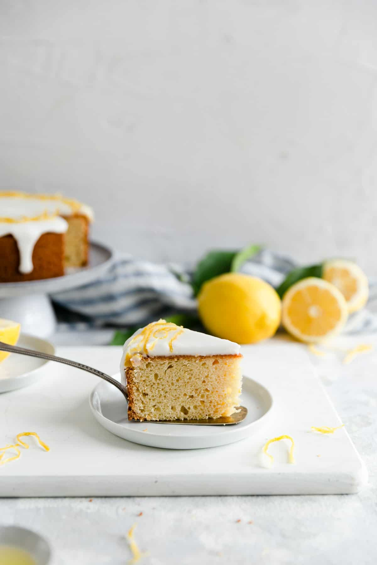 a side angle shot of one slice of zesty lemon cake on a small plate