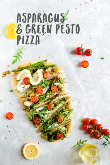 top view of slices of pizza topped with asparagus, green peas and cherry tomatoes
