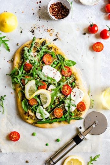overhead shot of homemade rocket and asparagus pizza with green peas and cherry tomatoes