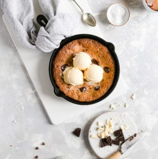 overhead shot of skillet cookie topped with 3 scoops of vanilla ice cream
